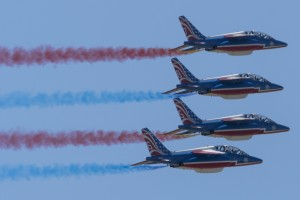 The outside wingmen and solos pass in a stacked formation trailing red and blue smoke.
